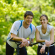 Happy couple riding bicycle outdoors — Stock Photo #11937286
