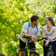 Happy couple riding bicycle outdoors — Stock Photo #11937312