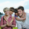 Stock Photo: Happy young family have fun outdoors