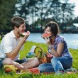Happy young couple having a picnic outdoor — Стоковая фотография