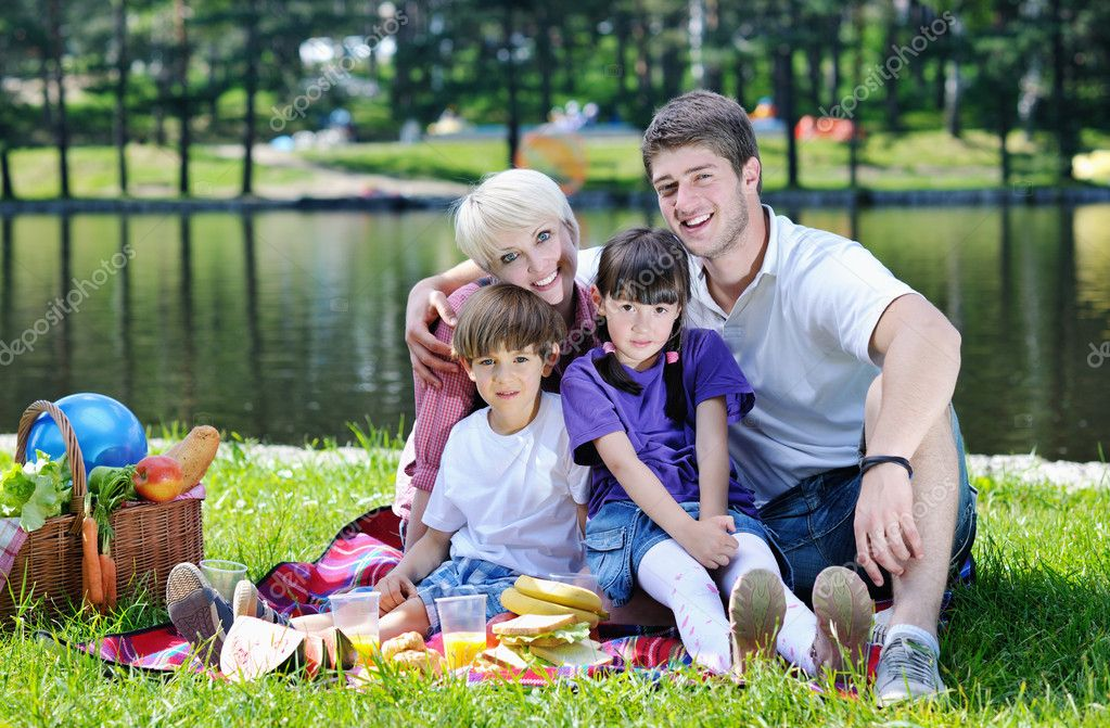 Happy young  family playing together with kids and eat healthy food  in a picnic outdoors — Stock Photo #11938332