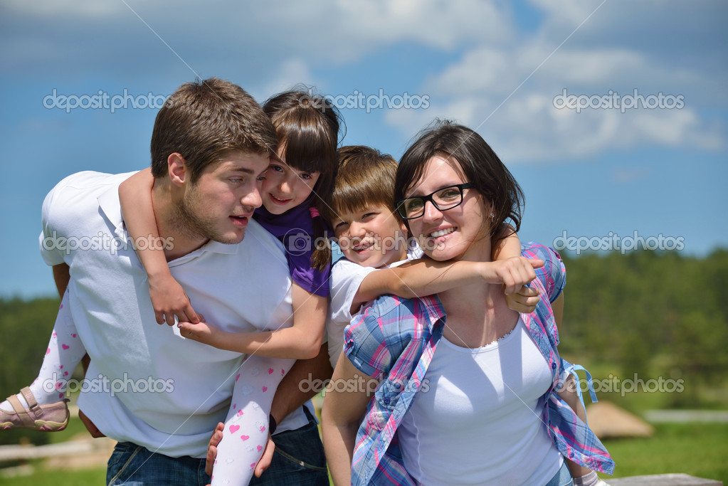 Happy young family with their kids have fun and relax outdoors in nature with blue sky in background — Stock Photo #11939118