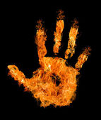 Human hand in orange flame on black — Stock Photo