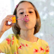 Little girl blows soap bubble — Stock Photo #12224993