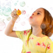 Little girl blows soap bubble — Stock Photo #12224997