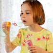 Little girl blows soap bubble — Stock Photo