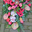 Pink sympathy bouquet on pavement — Stock Photo