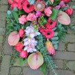 Pink sympathy bouquet on pavement — Stock Photo #11750624