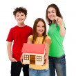 Stock Photo: Kids holding model of house isolated on white background