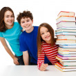 Students peeking behind pile of books on white background - Stock Photo