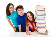 Students peeking behind pile of books on white background — Stock Photo