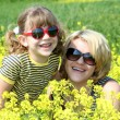 Happy mother and daughter in yellow flowers field — Stock Photo #11016519
