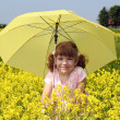 Stock Photo: Beautiful little girl with umbrellstanding in yellow flowers field