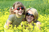 Happy mother and daughter in yellow flowers field — Stock Photo