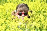 Bambina nascondendo nel campo di fiori gialli — Foto Stock