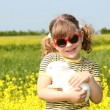 Stock Photo: Little girl with bunny pet in yellow field