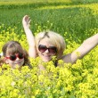 Mother and daughter in yellow flower field — Stock Photo