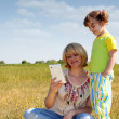 Mother and daughter with tablet in field — Stock Photo