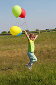 Little girl running on field with balloons — Foto Stock
