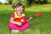 Ragazza piccola seduta sull'erba, suonare la chitarra e cantare — Foto Stock