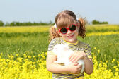 Little girl with bunny pet in yellow field — Стоковое фото