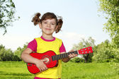 Little girl with guitar in park — Stock fotografie