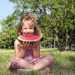 Stock Photo: Little girl sitting on grass and eat watermelon