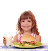 Besmear little girl with big sandwich — Stock Photo