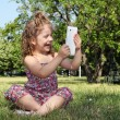 Stock Photo: Happy little girl with tablet in park