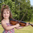 Stock Photo: Little girl play violin in park
