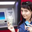 Stock Photo: woman withdrawing money from credit card at atm