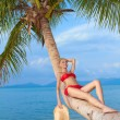 Woman reclining on a palm trunk - Stock Photo