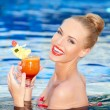 glad blondin innehar en drink medan i en pool — Stockfoto