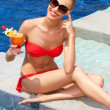 Pretty seated blonde in bikini with a drink — Stock Photo
