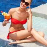 Pretty seated blonde in bikini with a drink — Stock Photo
