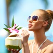 Woman drinking tropical cocktail - Stock Photo