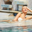 Beautiful blonde girl relaxing in the pool — Stock Photo