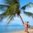 Woman leaning against a palm tree - Stock Photo
