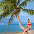 Graceful woman sitting on palm tree — Stock Photo