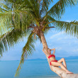 Стоковое фото: Woman in bikini reclining on palm tree trunk