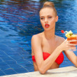 Beautiful blonde in a pool with a cocktail — Stock Photo