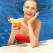 Laughing woman in a pool with a cocktail — Stock Photo #10863246