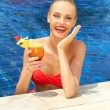 Laughing woman in a pool with a cocktail - Stock Photo