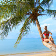Woman relaxing on the trunk of a palm tree — Stockfoto