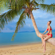 Woman sitting on palm tree at the beach — Stock Photo