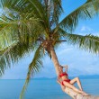 Woman suntanning on the trunk of a palm — Stock Photo