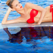 Pretty blonde reclining beside a swimming pool — Stock Photo #10863335