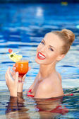 Happy blonde holding a drink while in a pool — Stock Photo