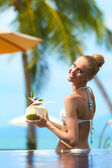 Smiling womanholding a tropical cocktail — Stock Photo