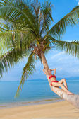 Woman in bikini reclining on palm tree trunk — Stock Photo
